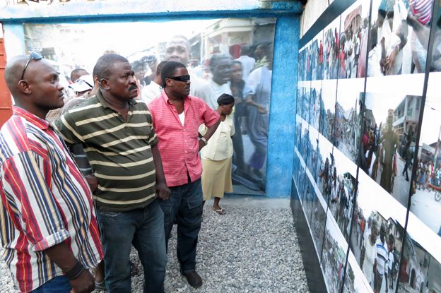 People looking at Morel's photos in Haiti
