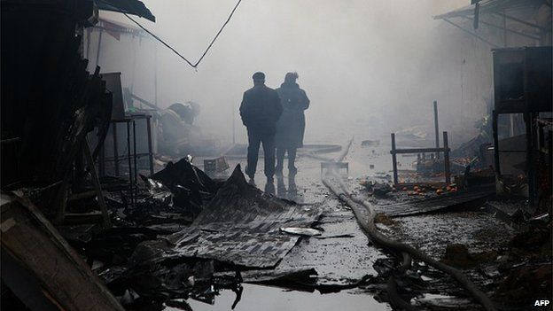 People walk past burnt out kiosks at a street market close to a destroyed building housing the housing the local media known as the Press House, in central Grozny, on December 4, 2014