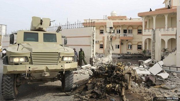 Armoured vehicle parked next to the wreck of a car that exploded outside the SYL Hotel in Mogadishu, Somalia - 22 January 2015