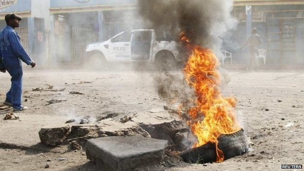 A man walks past a tyre set alight during a nationwide protest as opposition parties tried to block a change in the law that may delay elections - Goma, DR Congo, 19 January 2015