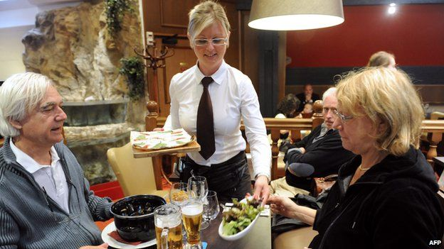 Waitress serves customers in French restaurant