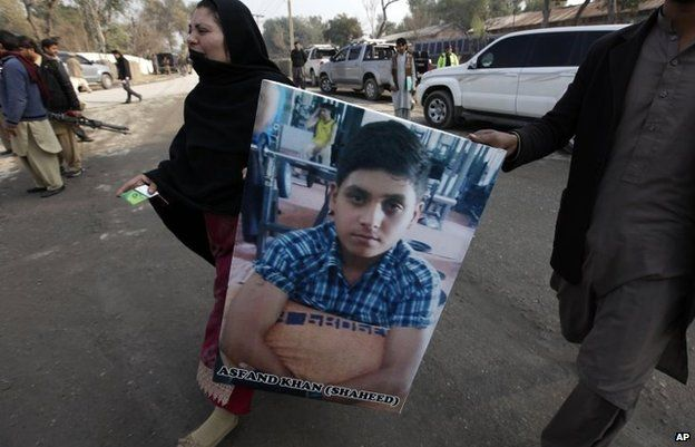 A Pakistani mother carries a picture of her son who was killed in the Taliban attack, January 14