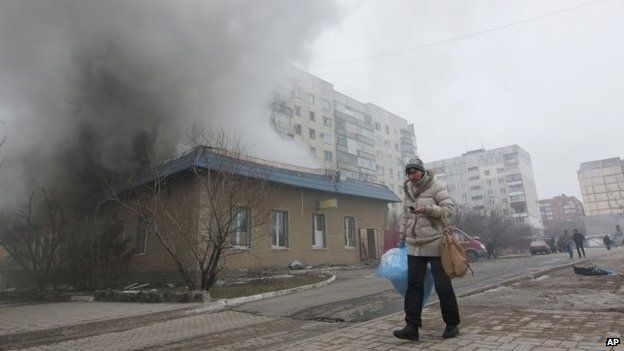 A woman resident passes by a burning house in Mariupol, Ukraine on 24 January 2015