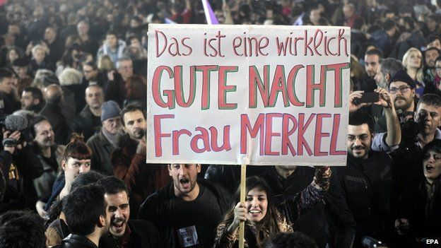 """Syriza supporters in Athens hold a poster: """"This is a really good night, Mrs Merkel"""""""