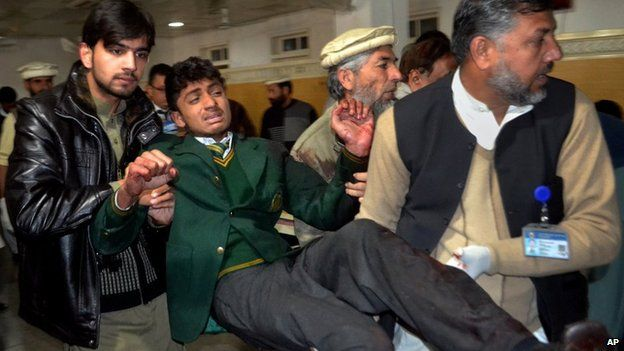 A student is helped after a gun attack at a school in Peshawar