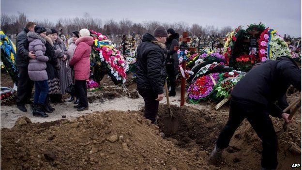 Relatives dig graves in Mariupol, 26 January 2015