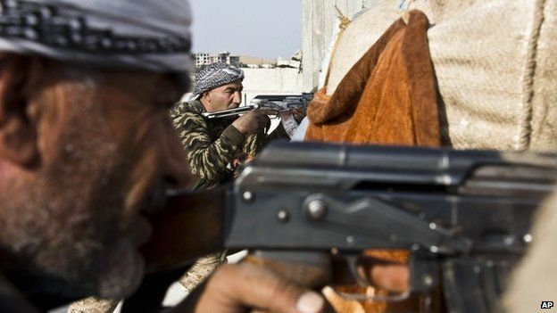 Fighters from the Popular Protection Units (YPG) and the Free Syrian Army (FSA) take aim during the battle for Kobane (19 November 2014)
