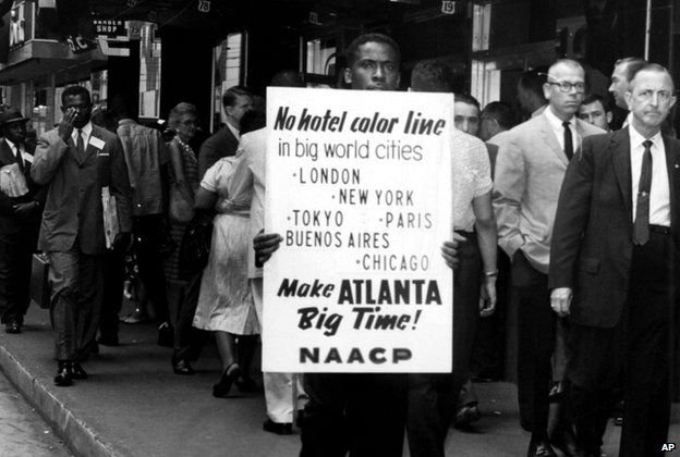 """Man protesting and holding a sign reading: """"No hotel color line"""""""