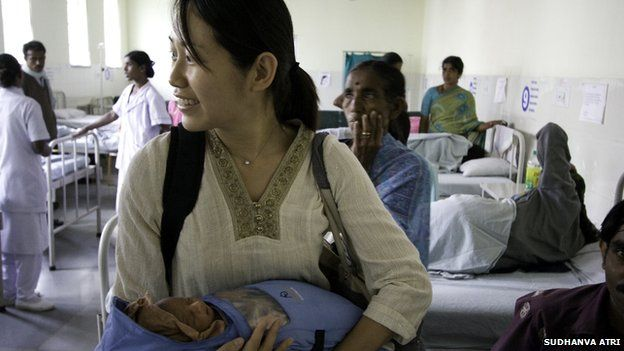 Jane Chen holding a baby wearing an Embrace baby warmer at a hospital in India