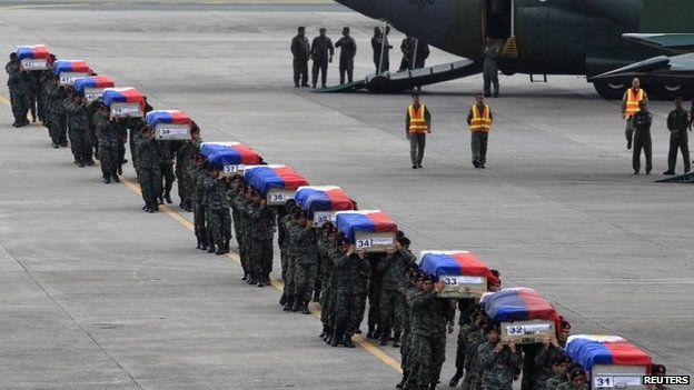 Members of the Philippine National Police's (PNP) Special Action Force (SAF) unit carry metal caskets containing the bodies of slain SAF police who were killed in Sunday's clash with Muslim rebels, upon arriving at Villamor Air Base in Pasay city, metro Manila on 29 January 2015