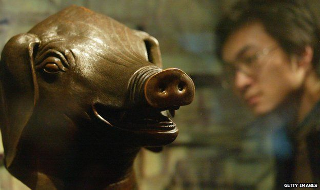 A man views the pig bronze head of Qing Dynasty (1644-1911) at a special exhibition April 28, 2005 in Shenyang of Liaoning Province, China. Four pieces of famous bronze heads including a tiger, a pig, an ox and a monkey of Qing Dynasty art treasure make their debut in Shenyang during the exhibition. They are among the 12 Chinese zodiac sculptures which originally placed in the Old Summer Palace in Beijing. The bronze set were taken out of the country in 1860 by British and French archaeologists. In 2000, the Beijing-based Poly Group bought the heads of the ox, tiger and monkey for more than RMB 30 million (USD 3.66 million) at an auction and returned them to the Chinese mainland. The pig head returned to China after it was purchased from the United States by Macao magnate Stanley Ho for RMB 6 million (USD 720,000) in 2003.