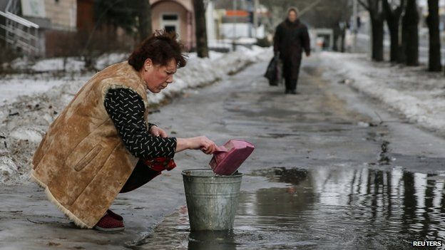 A woman gathers water from a puddle into a bucket in Donetsk. Photo: 31 January 2015