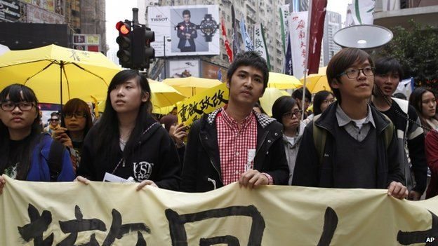 Student leader Alex Chow (centre) carries a banner with other students during the democracy march (01 February 2015)