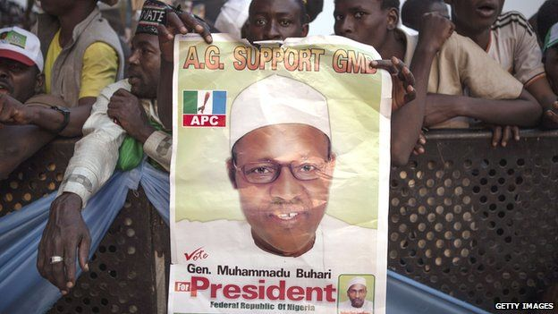 These supporters of the main Nigerian opposition All Progressive Congress (APC) party holds a campaing poster for Muhammadu Buhari, during a rally in Kaduna