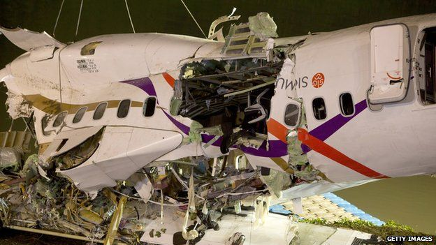 A close up of the upside down plane reveals the damage of the impact and rescue operation