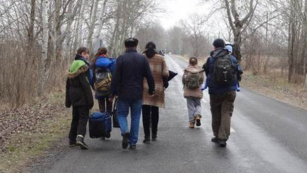 Migrants walk along the road in Asotthalom in Hungary