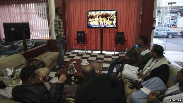 People watch television as an announcement by the Houthi movement on dissolving the parliament is made in Sanaa