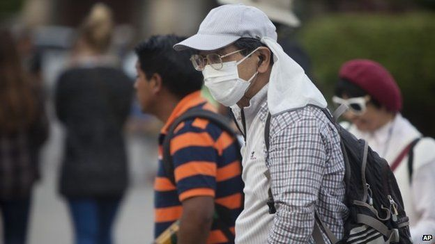 A tourist covers his face with a surgical mask as he walks to protect himself from the ash from the eruption of the Fuego Volcano at Antigua Guatemala, Saturday, Feb. 7, 2015