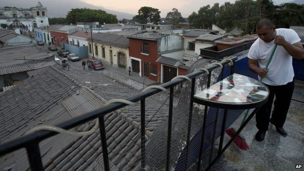 A waiter sweeps the ash covered terrace of a restaurant, from the eruption of the Fuego Volcano at Antigua Guatemala, Saturday, Feb. 7, 2015