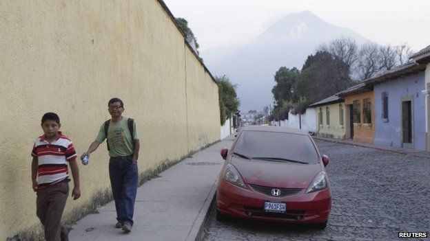 People walk near a car covered with ash in town of Antigua, on the outskirts of Guatemala City, February 7, 2015.