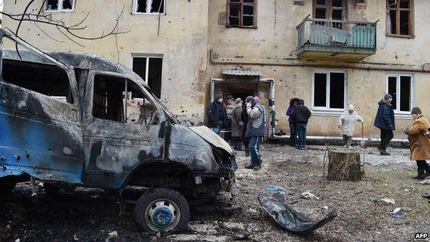 People clean a street near a destroyed car after shelling in the Leninsky district of the eastern Ukrainian city of Donetsk, 8 February 2015