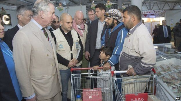 Prince Charles chats to shoppers while touring a supermarket at the Za'atri refugee camp in Jordan