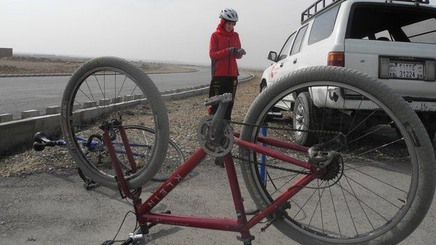 Woman mending her bike by the side of the road in Afghanistan, 2015.