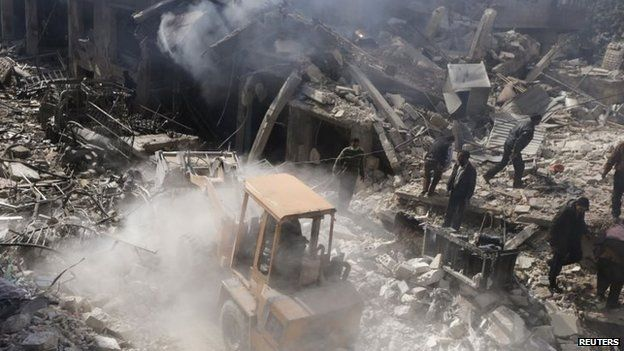 A man operates an excavator to remove rubble at a site hit by what activists said were airstrikes by forces loyal to Syria's President Assad in Douma