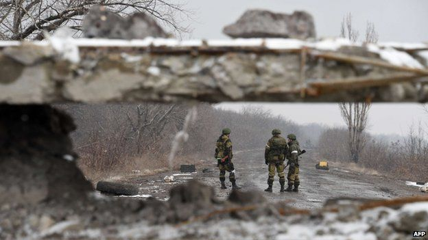Pro-Russian separatist fighters stand on 9 February 2015 on a road near Uglegorsk, 6 kms southwest of Debaltseve.