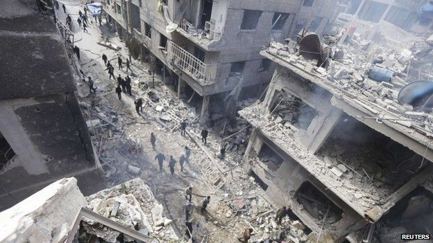 People inspect a site hit by what activists said were airstrikes by forces loyal to Syria's President Assad in Douma