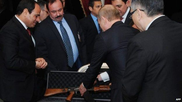 Russian President Vladimir Putin (second right) presents Egyptian President Abdul Fattah al-Sisi with a Kalashnikov AK-47 rifle before talks in Cairo (10 February 2015)
