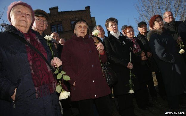 Visitors and survivors of the February 13, 1945 allied firebombing of Dresden, as well as Dresden Mayor Helma Orosz (fifth from right), arrive to lay white roses at the former train station where the Nazis shipped Dresden Jews to concentration camps