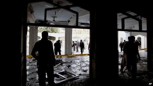 Members of the Pakistani security services stand at the scene of a suicide bomb blast targeting a Shia Mosque in Peshawar, Pakistan, 13 February 2015