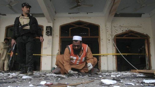 A rescue worker collects evidence from the site of an explosion in a Shia mosque in Peshawar 13 February 2015