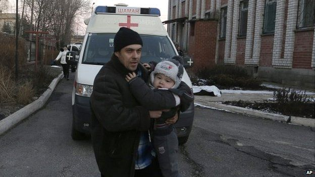 A man carries a child after shelling in a residential area of the town of Artemivsk, Ukraine - 13 February 2015
