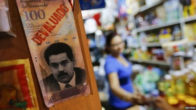 """President Nicolas Maduro and the word """"devaluated"""" is seen at a market in Caracas February 13, 2015."""