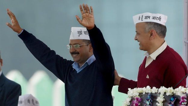 Aam Aadmi Party (AAP) president Arvind Kejriwal (L) greets his supporters as fellow Minister Manish Sisodia (R) congratulates him during his swearing-in ceremony as Delhi chief minister in Delhi on Saturday