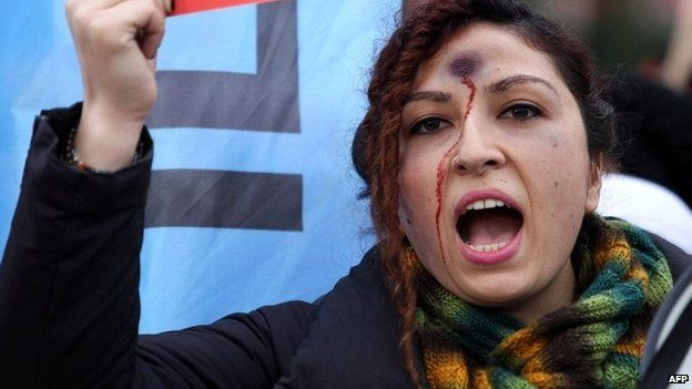 A woman with a bullet hole painted on her forehead takes part in a demonstration against the murder of 20-year-old Ozgecan Aslan, who was killed after she resisted an alleged attempt to rape her in the southern city of Mersin, in Ankara on Saturday