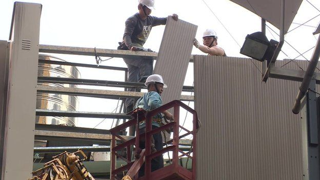 Video still of Taipei city workers demolishing illegal rooftops