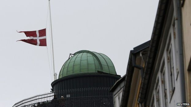 Danish flag at half-mast next to a memorial site for victims of the deadly attacks in Copenhagen 16/02/2015