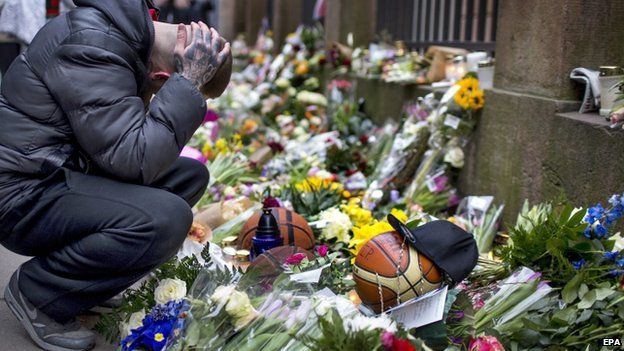 Man grieves next to flowers outside synagogue in Copenhagen 16/02/2015