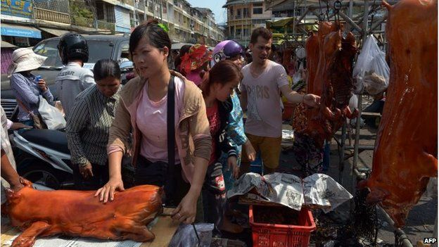 Woman packs a roasted pig at a new year fair in Phnom Penh, Cambodia