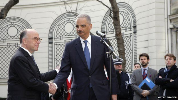 US Justice Minister Eric Holder (R) shakes hands with French Interior Minister Bernard Cazeneuve after their International meeting against terrorism at the Interior Ministry in Paris on January 11, 2015