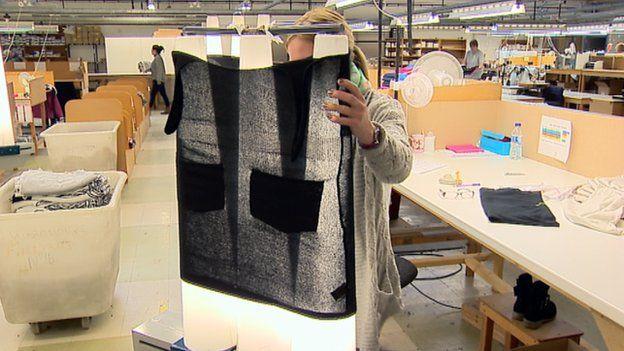 Woman inspects woollen garment
