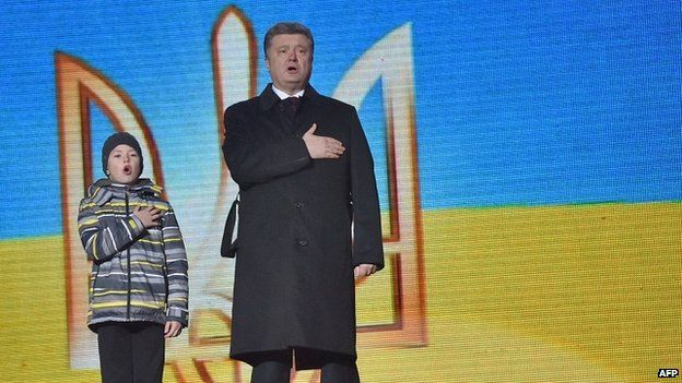 Ukrainian President Petro Poroshenko sings the state anthem with the son of a dead activist in Kiev - 20 February 2015