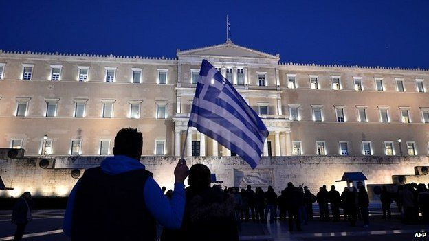 A man holds a Greek flag in front of the Greek parliament in Athens as people gather in support of their government - 20 February 2015