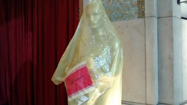 A giants Oscars statue in a plastic wrapper