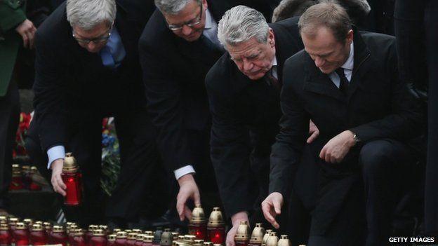 Polish President Bronislaw Komorowski (C), German President Joachim Gauck (R) and European Council president Donald Tusk (far right) lay candles to mark anniversary of uprising - 22 February