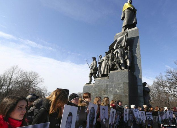 People hold portraits of local residents killed in fighting, during Kharkiv rally - 22 February