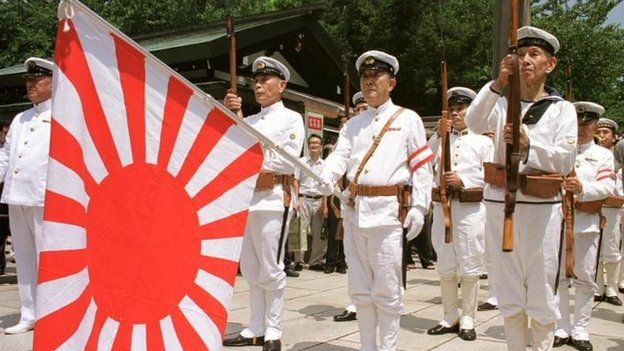 File photo of Japanese war veterans standing to attention with the navy flag as they pay their respect to the war dead at Tokyo's Yasukuni Shrine